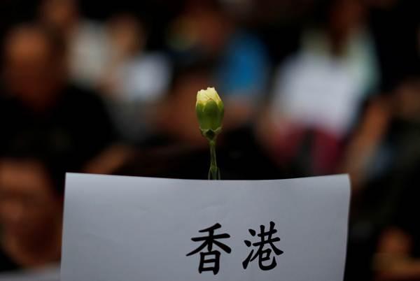 ผู้เข้าร่วมเดินขบวนประท้วงชูดอกไม้สนับสนุนผู้ประท้วง ภาพเมื่อวันที่ 14 มิ.ย. (ภาพ รอยเตอร์)