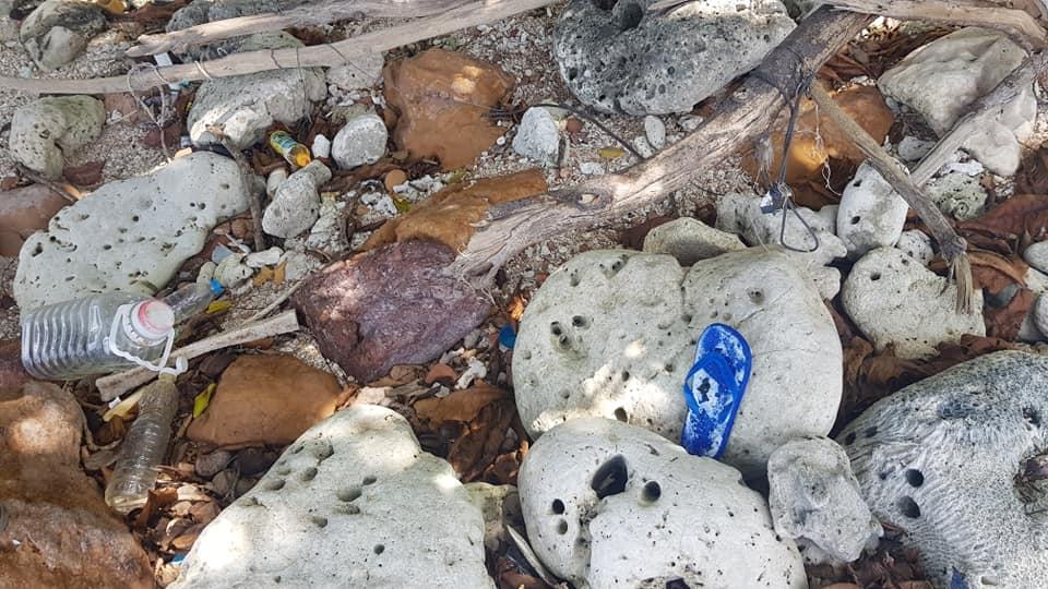 ขยะพลาสติกและขยะอื่นๆ ปะปนกับซากปะการังที่เสียหายจากพายุเกเมื่อหลายสิบปีก้อน