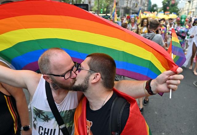 ผู้เข้าร่วมจูบกันและกันหน้าธงสีรุ้งในขณะที่พวกเขาเข้าร่วมพาเหรดเกย์ไพรด์ประจำปีในกรุงเคียฟ (23 มิ.ย.)