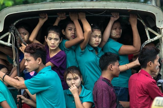 กลุ่มคนงานนั่งท้ายรถยนต์สองแถวเพื่อเดินทางไปโรงงานในเขตฮเลงตาร์ยาร์แถบชานเมืองย่างกุ้ง (26 มิ.ย.)