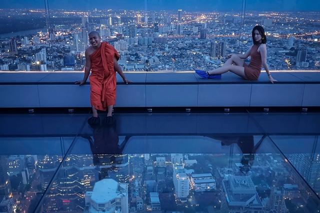 ภาพถ่ายเมื่อวันที่ 26 มิ.ย. เผยให้เห็นพระสงฆ์และนักท่องเที่ยวที่กำลังโพสต์ถ่ายรูปหน้าเส้นขอบฟ้าบนพื้นที่กลาสเทรย์ของมหานครสกายวอร์ค สูงจากพื้น 310 เมตร ในกรุงเทพ
