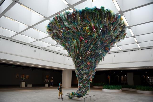 """เด็กหนุ่มยืนมองสถาปัตยกรรมชื่อว่า """"Tornado by plastic waste"""" ของศิลปินจากองค์กรทางสังคม To He ที่งานจัดแสดง """"Plastics Planet"""" ในฮานอย (27 มิ.ย.)"""