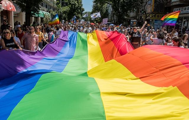 """ผู้เข้าร่วมถือธงสีรุ้งขนาดใหญ่ในขณะที่พวกเขาเข้าร่วมการเดินขบวน """"สโกเปียไพรด์"""" ใจกลางกรุงสโกเปียเมื่อวันที่ 29 มิ.ย. ในขณะที่มาซิโดเนียเหนือกำลังจัดขบวนพาเหรดเกย์ไพรด์เป็นครั้งแรก"""
