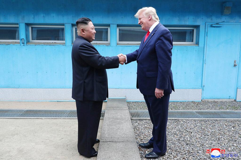 <i>(ภาพที่เผยแพร่โดยสำนักข่าวเคซีเอ็นเอของทางการเกาหลีเหนือ)  ผู้นำเกาหลีเหนือ และผู้นำสหรัฐฯ จับมือกันตรงบริเวณเส้นแบ่งแดน ณ หมู่บ้านปันมุนจอม ในเขตปลอดทหาร </i>