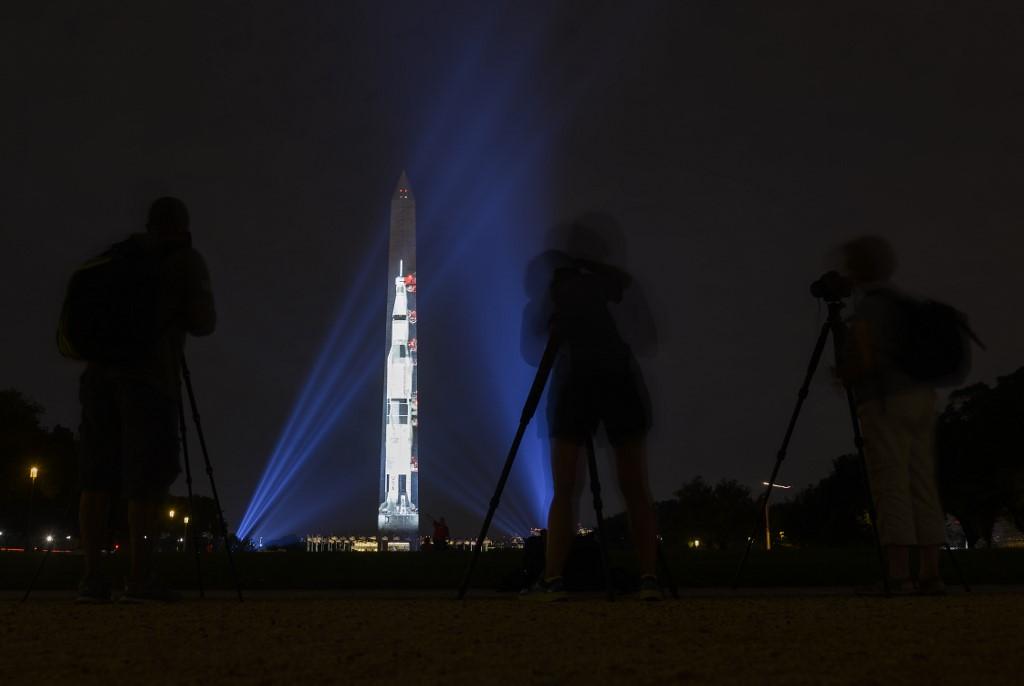 ประชาชนถ่ายภาพจรวดแซทเทิร์น 5 ที่ฉายบนอนุสาวรีย์วอชิงตัน (ANDREW CABALLERO-REYNOLDS / AFP)