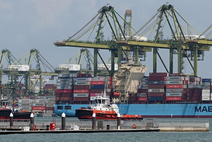 เรือสินค้าคอนเทนเนอร์ลำหนึ่งเข้าเทียบท่าเรือคอนเทนเนอร์ชายฝั่งด้านตะวันตกของสิงคโปร์ โดยตามข้อมูลล่าสุด การส่งออกและอัตราเติบโตของจีดีพีของสิงคโปร์กำลังทรุดตัว