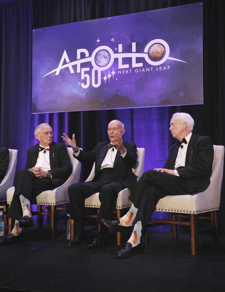 ไมเคิล คอลลินส์ (กลาง) บรรยายระหว่างงานฉลอง 50 ปี ส่งคนไปดวงจันทร์ โดยมี ชาร์ลี ดุค (Charlie Duke) ลูกเรืออะพอลโล 16 (ซ้าย) และ รัสตี ชไวค์การ์ท (Rusty Schweickart) ลูกเรืออะพอลโล 9 ร่วมด้วย (Gregg Newton / AFP)