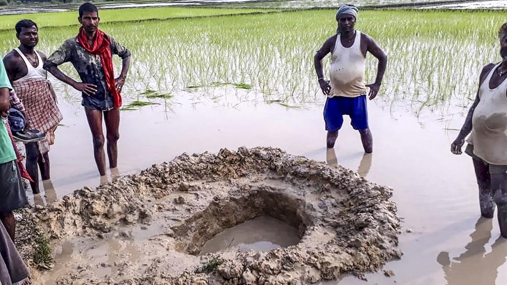 ชาวนาและชาวบ้านในอินเดีย ล้อมรอบหลุมที่คาดว่าเกิดจากอุกกาบาตหนักประมาณ 10 กิโลกรัม ตกใส่ทุ่งนา (STR / AFP)