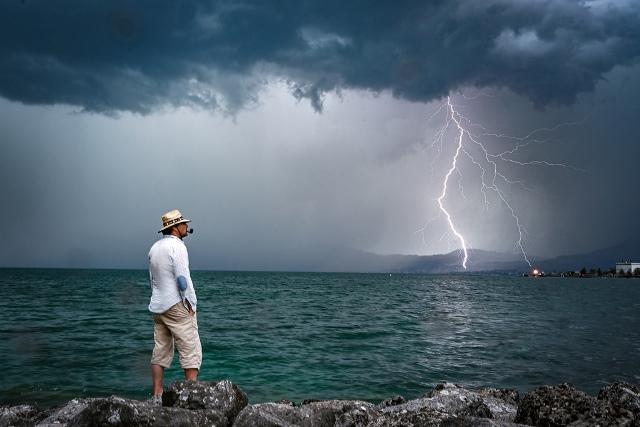 ชายคนหนึ่งยืนบนก้อนหินในขณะที่ฟ้าผ่าเหนือทะเลสาบเจนีวาเมื่อวันที่ 6 ส.ค. ใกล้เมืองเลอบูเวเร็ต ภาคตะวันตกของสวิตเซอร์แลนด์