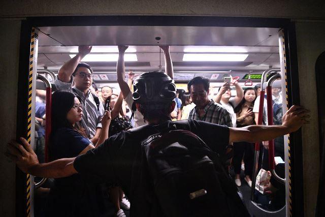 ผู้ประท้วงคนหนึ่งขวางไม่ให้รถไฟใต้ดินขบวนหนึ่งปิด ในขณะที่ผู้ประท้วงหลายคนขวางประตูรถไฟที่สถานทีฟอร์เทรสฮิลล์ในฮ่องกงเมื่อวันที่ 5 ส.ค. ในความพยายามเพื่อรบกวนการสัญจรชั่วโมงเร่งด่วนตอนเช้า