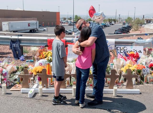 สมาชิกครอบครัวโซโตกอดกันข้างๆ อนุสรร์ชั่วคราว หลังเหตุกราดยิงทำให้มีผู้เสียชีวิต 22 คนที่ Cielo Vista Mall WalMart ในเอลปาโซ รัฐเท็กซัส เมื่อวันที่ 5 ส.ค.