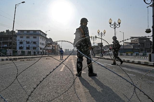 ภาพถ่ายเมื่อวันที่ 5 ส.ค. เผยให้เห็นกองกำลังกึ่งทหารของอินเดียยืนคุ้มกันหลังรั้วลวดหนาม ในขณะที่พวกเขาปิดถนนเส้นหนึ่งในระหว่างเคอร์ฟิวในเมืองศรีนาการ์