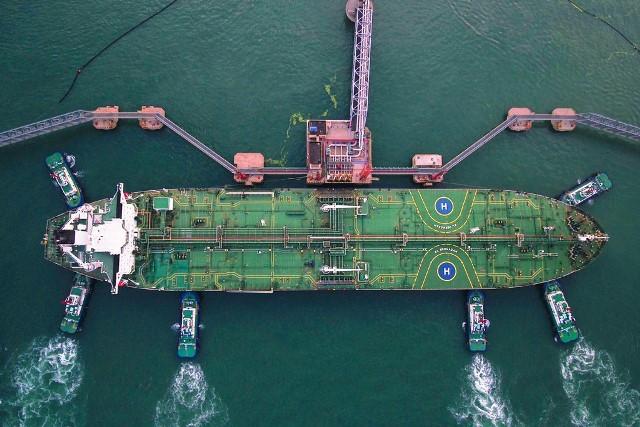 ภาพถ่ายทางอากาศเมื่อวันที่ 4 ส.ค. เผยให้เห็นเรือโยงจอดเทียบเรือบรรทุกน้ำมันลำหนึ่งในท่าเรือชิงเต่าในเมืองชิงเต่าในมณฑลชานตงของจีน