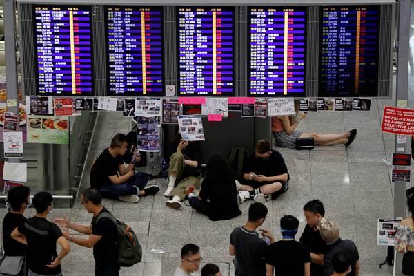 ผู้ประท้วงที่ยังหลงเหลือที่สนามบินนานาชาติฮ่องกงในตอนเช้าวันอังคาร ปละประกาศว่าจะกลับมารวมตัวกันอีกในตอนบ่าย ภาพ 13 ส.ค. (ภาพ รอยเตอร์ส)