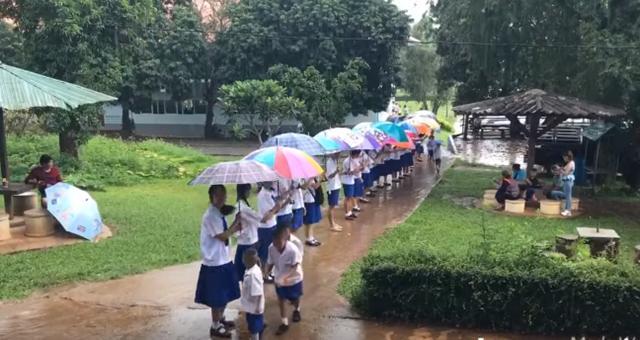 อบอุ่น! พี่มัธยมพร้อมใจยืนต่อแถวกางร่มให้น้องๆประถม ในวันที่ฝนตก (ชมคลิป)