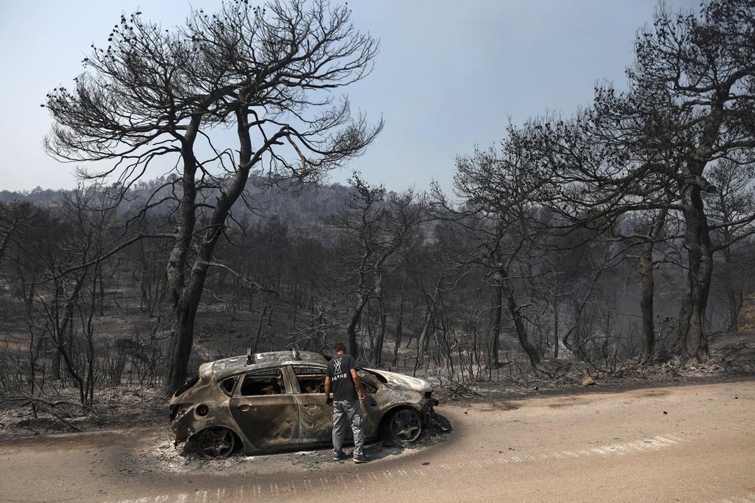 ชายคนหนึ่งกำลังมองซากรถที่ถูกเผาจากไฟป่าในหมู่บ้านมาครีมาลลี (Makrymalli) บนเกาะเอเวีย(Evia) ทั้งเครื่องบินและเฮลิคอปเตอร์ที่ขนน้ำเพื่อดับไฟกลับมาเริ่มทำงานอีกครั้งในช่วงเช้าเพื่อดับไฟป่าที่กำลังเผาผลาญเขตสงวนบนเกาะ มีการสั่งอพยพประชาชนในพื้นที่ออกจากหมู่บ้าน 4 แห่งและอารามอีก 1 แห่ง ภาพวันพุธ(14) ภาพเอพี