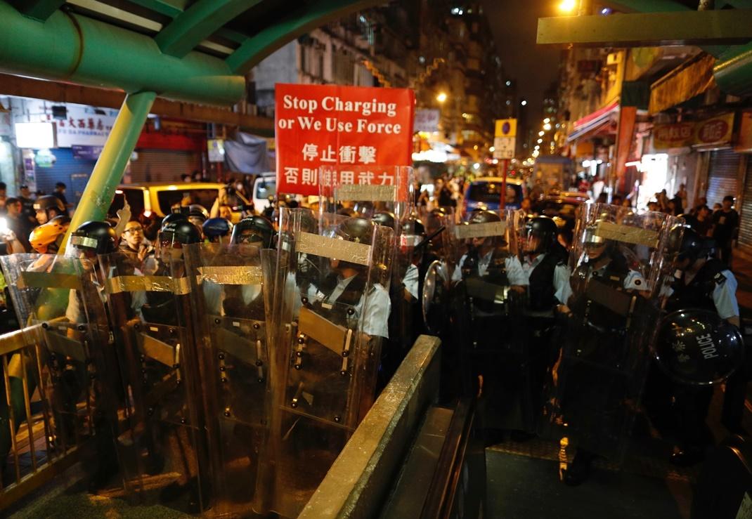 ตำรวจฮ่องกงกำลังเดินออกมาจากสถานีตำรวจซั้ม-โสย-โป๋ว(Shum Shui Po)เพื่อควบคุมการประท้วง ภาพวันพุธ(14) ภาพเอพี