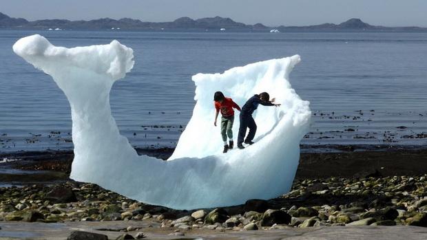 เด็กๆกำลังเล่นบนก้อนน้ำแข็งบริเวณชายหาดแห่งหนึ่งบนเกาะกรีนแลนด์