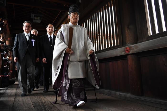<i>บรรดาสมาชิกรัฐสภาญี่ปุ่น เดินตามพระในศาสนาชินโต (กลาง) ภายหลังประกอบพิธีสักการะในศาลเจ้ายาสุกุนิ กรุงโตเกียว เมื่อวันที่ 15 สิงหาคม </i>