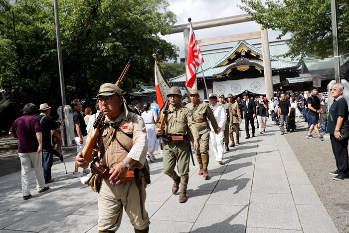 <i>กลุ่มชายแต่งกายด้วยเครื่องแบบกองทหารจักรพรรดิญี่ปุ่น ช่วงสงครามโลกครั้งที่ 2 เดินแถวเข้าศาลเจ้ายาสุกุนิ วันที่ 15 สิงหาคม </i>