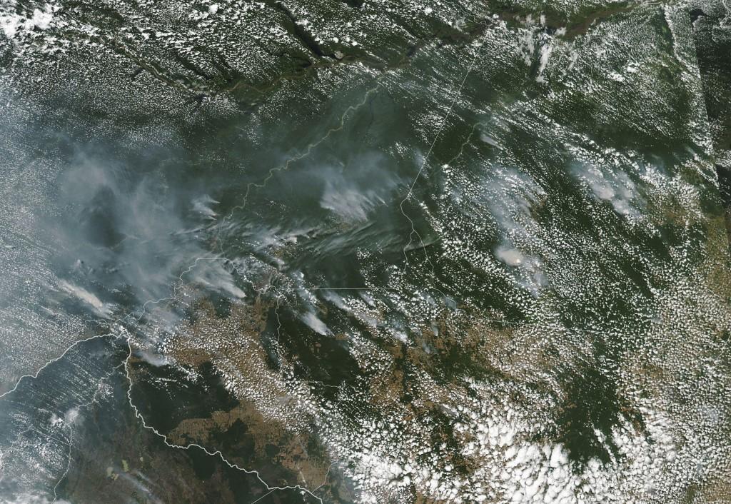 ภาพจากกล้อง MODIS บนดาวเทียมอควา (Aqua satellite) ขององค์การบริหารการบินอวกาศสหรัฐฯ (นาซา) เผยให้เห็นหมอกควันจากไฟป่าอเมอซอนในหลายรัฐของบราซิล (Lauren Dauphin / NASA Earth Observatory / AFP)