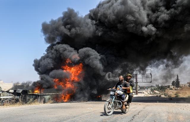 ชายสองคนขับมอเตอร์ไซค์ผ่านกลุ่มควันจากกองไฟที่จุดนัดรวมรถสำหรับพลเรือนที่จะหนีออกจากตอนใต้ของจังหวัดอิดลิบ ซึ่งมีรายงานว่าเป็นผลจากการทิ้งระเบิดของกองกำลังรัฐบาลซีเรีย