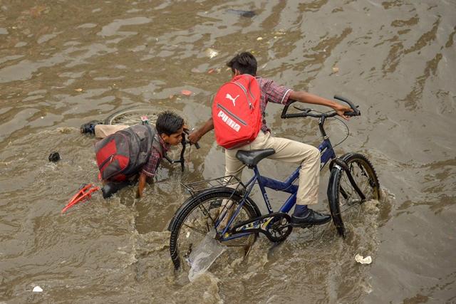 เด็กนักเรียนคนหนึ่งพยายามช่วยเหลือเพื่อนในขณะที่พวกเขาพยายามฝ่าน้ำท่วมหลังฝนมรสุมหนักในเมืองอัจเมอร์ เมื่อวันที่ 27 ส.ค.