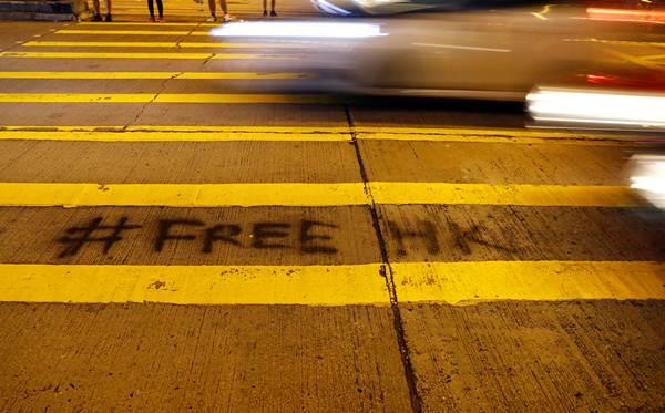 """ผู้ประท้วงเขียนอักษร """"ปลดปล่อยฮ่องกง"""" บนทางเท้าใกล้สถานีตำรวจมงก๊อก ฮ่องกง ภาพ 7 ก.ย. (ภาพ รอยเตอร์ส)"""