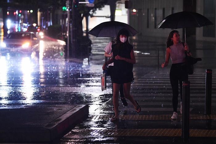 """<i>ผู้คนข้ามถนนในกรุงโตเกียวท่ามกลางสายฝนเมื่อคืนวันอาทิตย์ (8 ก.ย.)  ขณะไต้ฝุ่น """"ฟ้าใส"""" เคลื่อนใกล้เข้ามา </i>"""