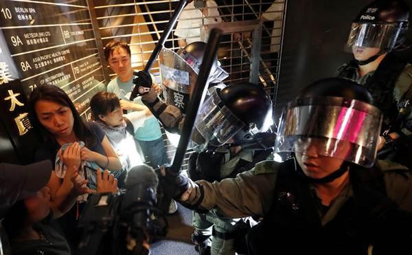 ตำรวจกำลังจับกุมตัวผู้ประท้วงที่สถานีคอสเวย์เบย์