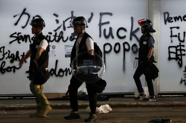 ผู้ประท้วงเดินไปตามถนนที่เต็มไปด้วยตัวขีดเขียน (ภาพ รอยเตอร์ส)
