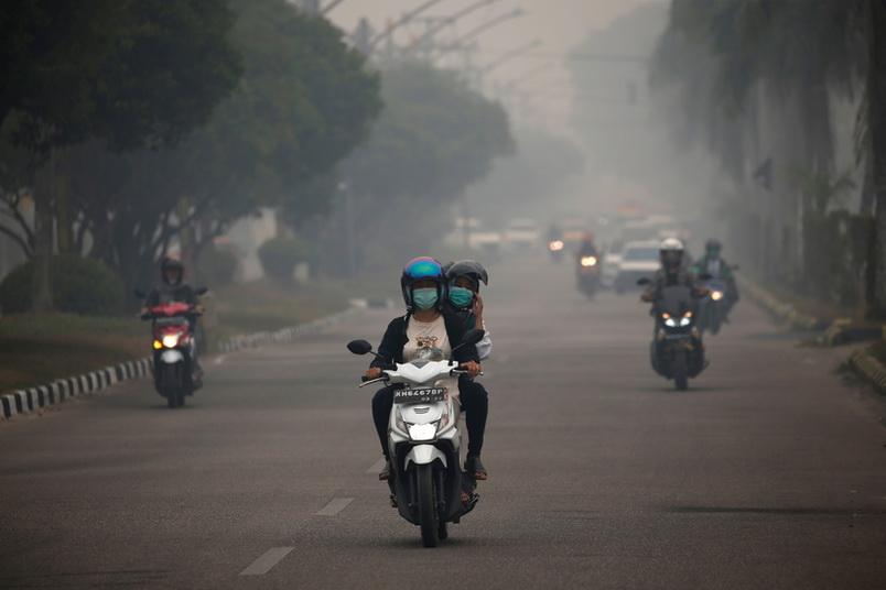 ชาวอินโดนีเซียขับขี่ยานพาหนะท่ามกลางทัศนวิสัยที่ย่ำแย่จากหมอกควันไฟป่าในเมืองปาลังการายา จังหวัดกาลิมันตันกลาง เมื่อวันที่ 15 ก.ย.