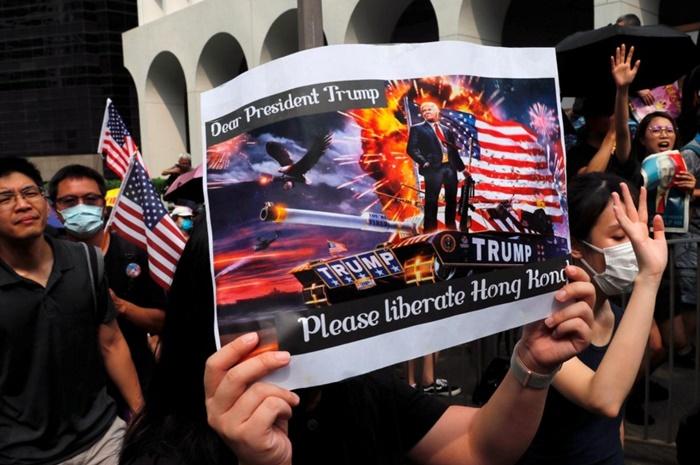 <i>กลุ่มผู้ประท้วงฮ่องกงไปชุมนุมหน้าสถานกงสุลสหรัฐฯเมื่อต้นเดือนกันยายน โดยโบกธงชาติสหรัฐฯ และร้องเพลงชาติสหรัฐฯ พร้อมกับถือป้ายวอนให้ประธานาธิบดีทรัมป์ช่วยปลดแอกฮ่องกงจากจีน </i>