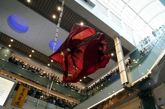กลุ่มประท้วงต่อต้านรัฐบาลทำลายธงชาติจีนกลางห้างนิว ทาวน์ พลาซ่า (New Town Plaza) ที่ชาทิน ฮ่องกง ภาพ 22 ก.ย. 2019 (ภาพ รอยเตอร์ส)
