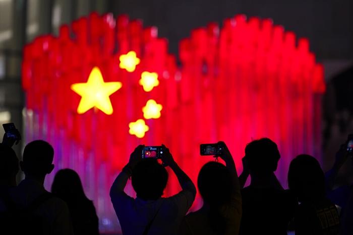 <i>ผู้ชมพากันใช้สมาร์ทโฟนถ่ายภาพการแสดงสดที่ทำเป็นภาพธงชาติจีนรูปหัวใจ เมื่อวันศุกร์ (27 ก.ย.) ที่นครเซี่ยงไฮ้  ประเทศจีน  ทั้งนี้จีนจะเฉลิมฉลองวาระครบรอบ 70 ปีของการก่อตั้งประเทศในวันอังคาร (1 ต.ค.) </i>