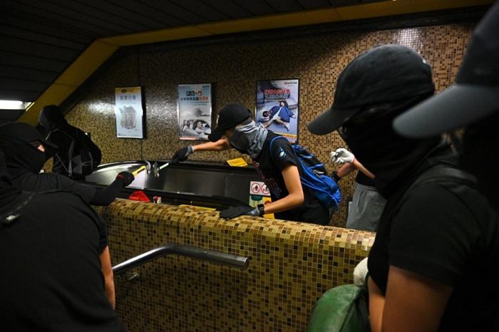 "<i>กลุ่มผู้ประท้วงสวมหน้ากาก บุกทุบทำลายสถานีรถไฟใต้ดิน ""ไดมอนด์ฮิลล์"" ในเขตเกาลูน ของฮ่องกง เมื่อวันจันทร์ (7 ต.ค.) </i>"