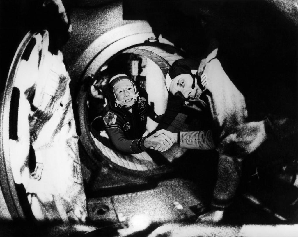 (ซ้าย) อะเล็กซี ลีโอนอฟ (ขวา) จับมือกับ โทมัส สตัฟฟอร์ด (Thomas Stafford) มนุษย์อวกาศสหรัฐฯ ระหว่างการซ้อมเชื่อมต่อของยานโซยุซและยานอะพอลโล  เมื่อ 17 ก.ค.1975 (HO / NASA / AFP)