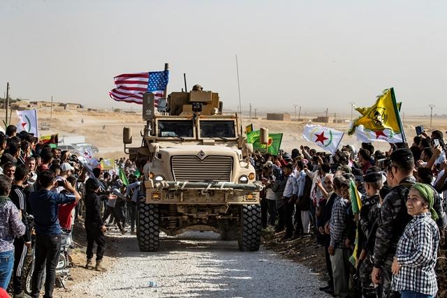 ชาวเคิร์ดในซีเรียล้อมรอบยานยนต์หุ้มเกราะสหรัฐฯ ในระหว่างการประท้วงต่อต้านการข่มขู่จากตุรกีข้างๆ ฐานทัพกลุ่มพันธมิตรนานาชาติที่นำโดยสหรัฐฯ ชานเมืองราสอัลอินในจังหวัดฮาซาเกห์ของซีเรียใกล้ชายแดนตุรกี