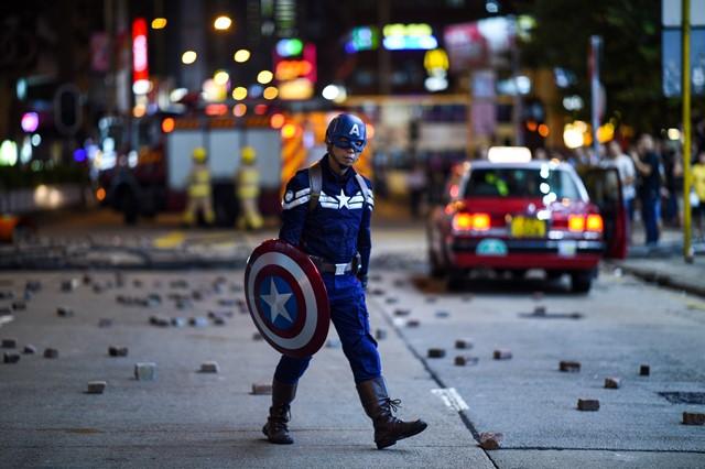 ชายคนหนึ่งที่สวมชุดกัปตันอเมริกากำลังเดินบนถนนเส้นหนึ่ง ในขณะที่ผู้ประท้วงและคนทั่วไปรวมตัวกันใกล้สถานีตำรวจมงก๊กในฮ่องกง