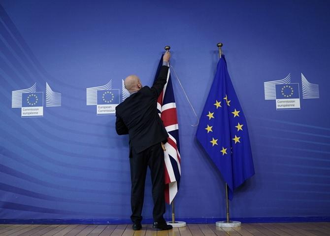 เจ้าหน้าที่ผู้หนึ่งแขวนธงชาติอังกฤษข้างๆ ธงของสหภาพยุโรป ณ สำนักงานใหญ่ของอียู ในกรุงบรัสเซลส์ เมื่อวันพฤหัสบดี (17 ต.ค.) ก่อนหน้าการประชุมซัมมิตอียูว่าด้วยเรื่องเบร็กซิต  โดยที่ไม่กี่ชั่วโมงก่อนซัมมิตจะเริ่มต้น  ผู้นำของอังกฤษและอียูแถลงว่าสามารถทำดีลฉบับใหม่ได้เรื่องนี้ได้สำเร็จแล้ว