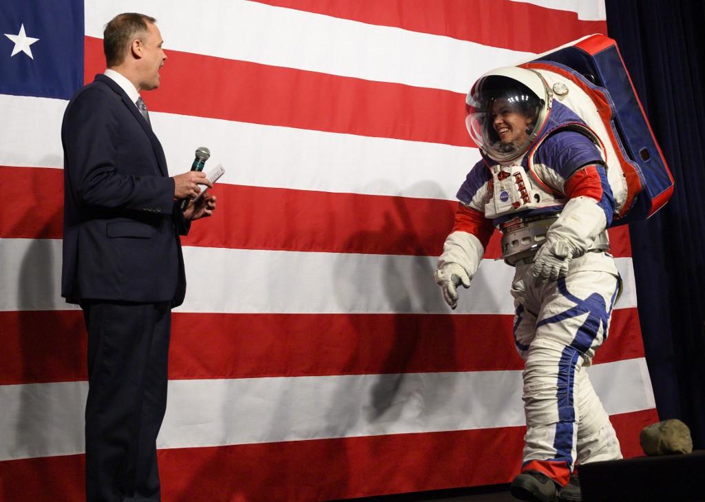 จิม ไบรเดนสไตน์ รับหน้าที่พิธีกรเปิดตัวชุดอวกาศรุ่นใหม่ของนาซา ที่นำเสนอโดย คริสติน เดวิส วิศวกรชุดอวกาศ(Andrew CABALLERO-REYNOLDS / AFP)
