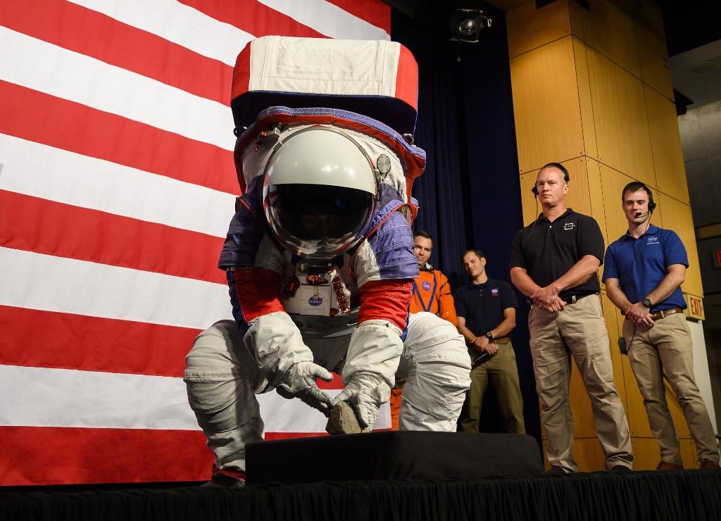 คริสติน เดวิส วิศวกรชุดอวกาศของนาซา สาธิตก้มเก็บก้อนหินขณะสวมชุดเอกซ์อีเอ็มยู (Andrew CABALLERO-REYNOLDS / AFP)