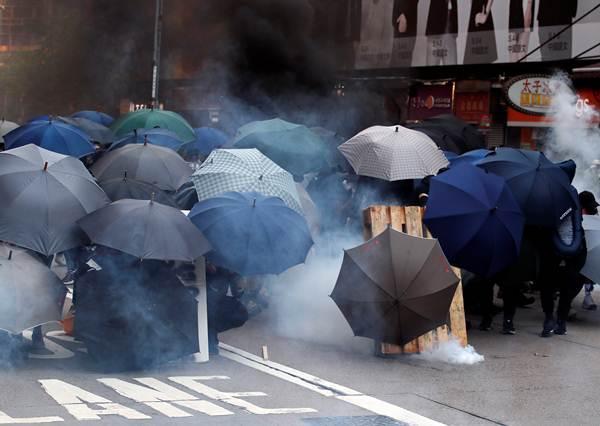 ผู้ประท้วงใช้ร่มกันแก๊สน้ำตา ภาพ 20 ต.ค. (ภาพ รอยเตอร์ส)