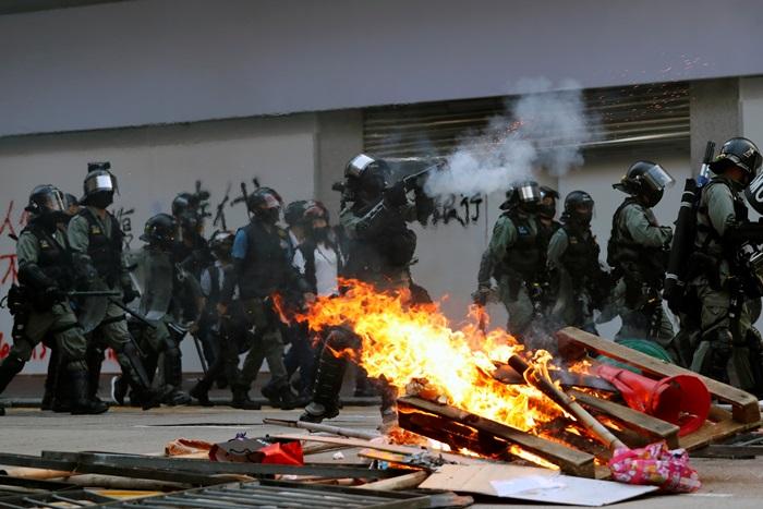 <i>ตำรวจปราบจลาจลยิงแก๊สน้ำตา ใกล้ๆ กับแนวเครื่องกีดขวางที่ไฟกำลังลุกไหม้ซึ่งพวกผู้ประท้วงสร้างเอาไว้ </i>