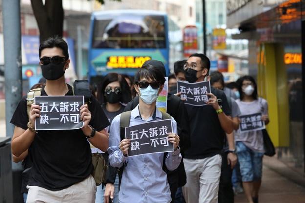 """In Clip: มาแนวใหม่! """"ผู้ประท้วงฮ่องกง"""" สวมหน้ากาก-แต่งชุดดำ ถือป้ายประท้วงระหว่างไปทำงานตอนเช้า"""