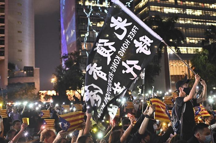 "<i>(ภาพถ่ายเมื่อ 24 ต.ค. 2019) หนุ่มผู้หนึ่งโบกธงที่เขียนข้อความว่า ""ปลดปล่อยฮ่องกง การปฏิวัติแห่งยุคสมัย""  ขณะที่คนอื่นๆ ถือธง ""เอสเตลาดา"" ของพวกผู้เรียกร้องแยกแคว้นกาตาลุญญาเป็นประเทศเอกราช ระหว่างการชุมนุมของพวกผู้ประท้วงฮ่องกงเพื่อแสดงความสมานฉันท์กับผู้ประท้วงชาวกาตาลุญญา </i>"