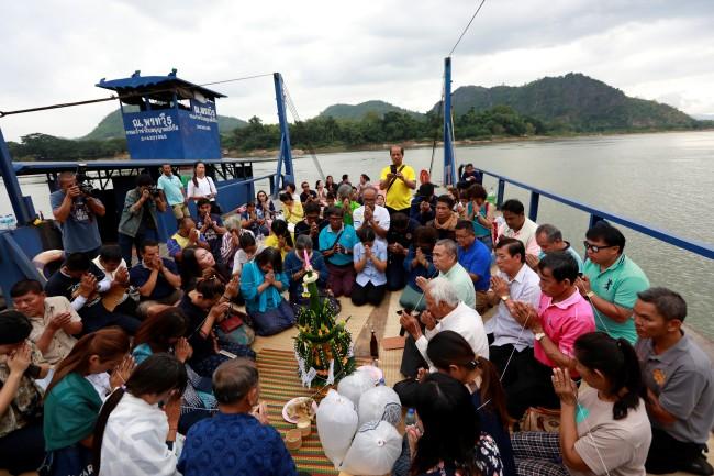 นักเคลื่อนไหวและชาวบ้านร่วมทำพิธีทางศาสนาเพื่อประท้วงคัดค้านโครงการเขื่อนในลาว ที่ริมฝั่งแม่น้ำ จ.เลย. -- Reuters.