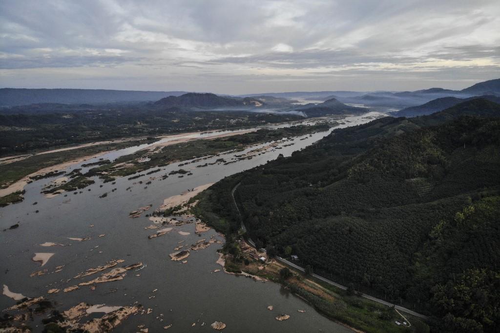 ภาพทางอากาศของแม่น้ำโขงอันแห้งขอด ที่เห็นลาวอยู่ฝั่งซ้าย และ อ.สังคม จ.หนองคาย อยู่ฝั่งขวา โดยระดับน้ำที่ลดต่ำเป็นประวัติการณ์นี้ถูกลา่วโทษว่ามีสาเหตุจากภัยแล้ง และเขื่อนที่อยู่ต้นน้ำห่างไปหลายร้อยกิโลเมตร  (Lillian SUWANRUMPHA / AFP)