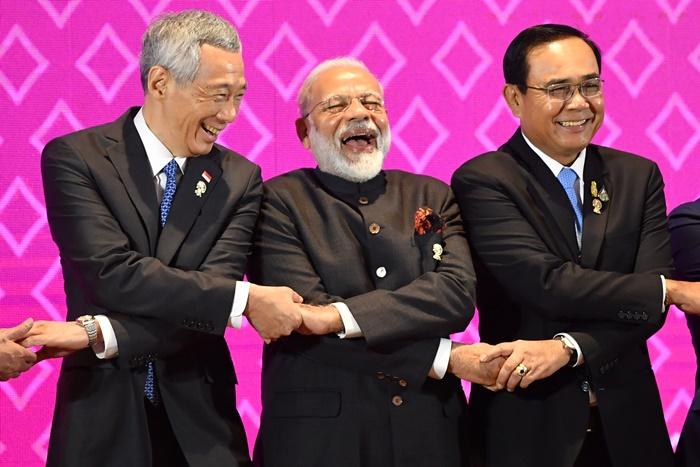 <i>นายกรัฐมนตรีลี เซียนลุง ของสิงคโปร์ (ซ้าย) กับ นายกรัฐมนตรีนเรนทรา โมดี ของอินเดีย (กลาง) หัวเราะร่าข้างๆ นายกรัฐมนตรี พล.อ.ประยุทธ์ จันทร์โอชา ขณะเตรียมถ่ายภาพหมู่ ระหว่างการประชุมสุดยอดอินเดีย-อาเซียน เมื่อวันอาทิตย์ (3 พ.ย.) </i>
