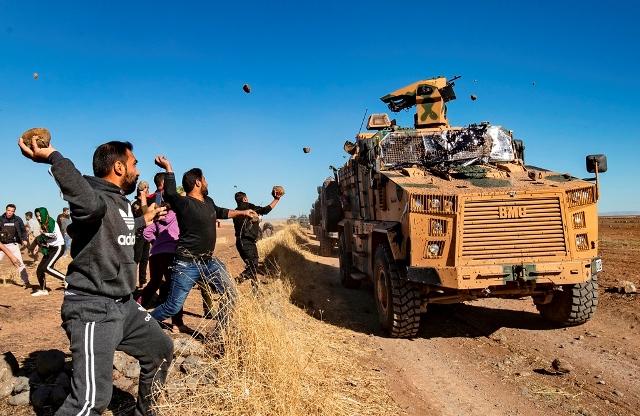 กลุ่มผู้ชุมนุมชาวเคิร์ดขว้างปาหินใส่ยานพาหนะทหารตุรกีคันหนึ่งเมื่อวันที่ 8 พ.ย. ในระหว่างการลาดตระเวนร่วมตุรกี-รัสเซียใกล้เมืองอัลมูอับบาดาห์ในส่วนตะวันออกเฉียงเหนือของจังหวัดฮัสซากาห์บริเวณชายแดนซีเรียติดตุรกี